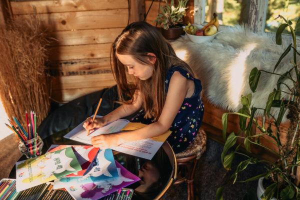 Kind malt in dem Ausmalbuch von Familie Bunt