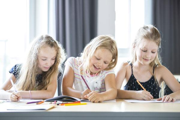 Drei Mädchen malen in Ausmalbüchern von Familie Bunt